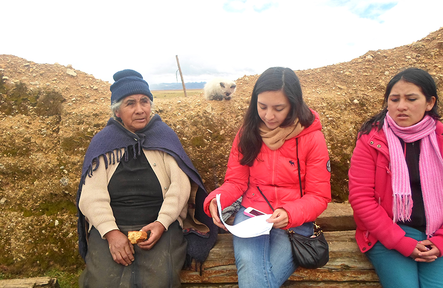 REES reseacher Maria Montenegro and her research assistant sit outside in rural Peru interviewing an older female farmer.