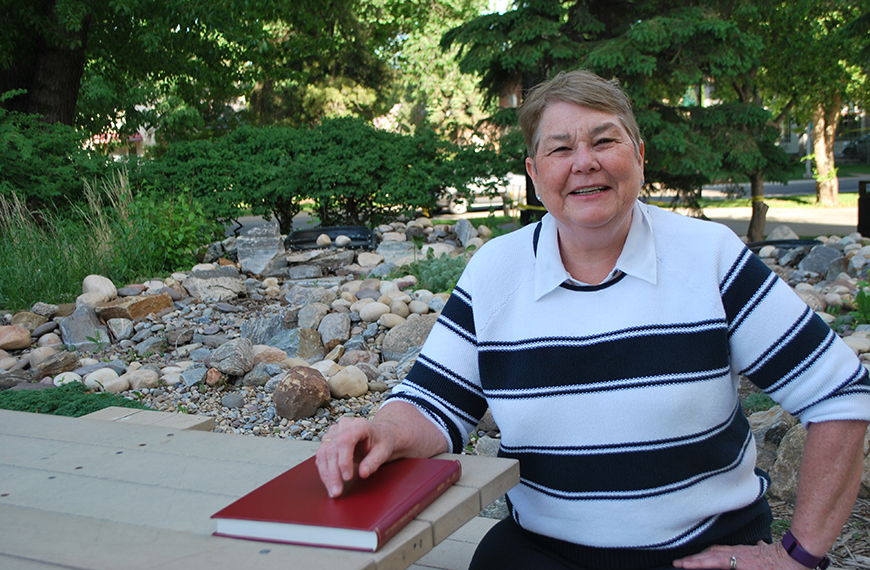 New Human Ecology PhD grad Sharon Anderson sits at a picnic table in the ALES garden with her red leather-bound PhD thesis, which examines what happens to marriages when one spouse suffers a stroke.