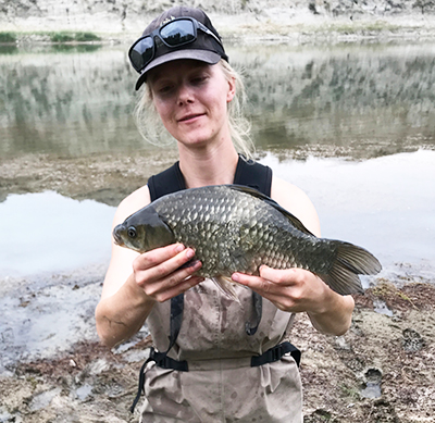 MSc student Cait Donadt stands on river bank holding a very large Prussian carp that's approximately 30 centimetres long.
