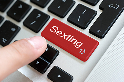 "Closeup of a finger on a corner of a computer keyboard, about to push a large red button labelled ""Sexting"". IStock image."