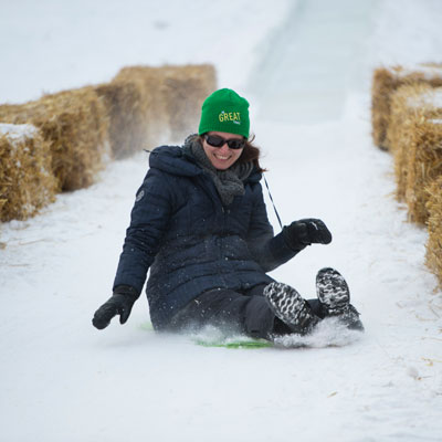 Woman tobogganing at Green & Glow Winterfest