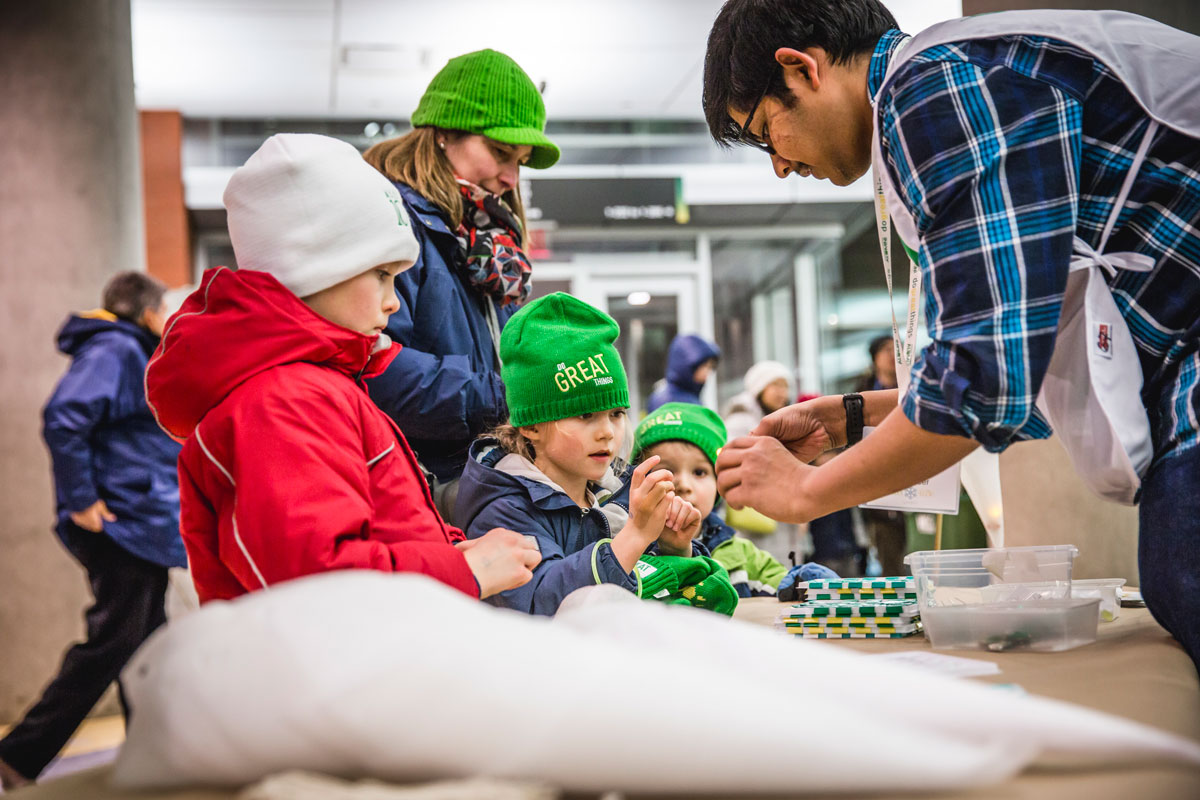 Engineering student and volunteer Preetam Anbukarasu helps the future generation of UAlberta students build lanterns while alumna and mom Kirstin Boelman, '95 BA, '01 BSc(OT) looks on.
