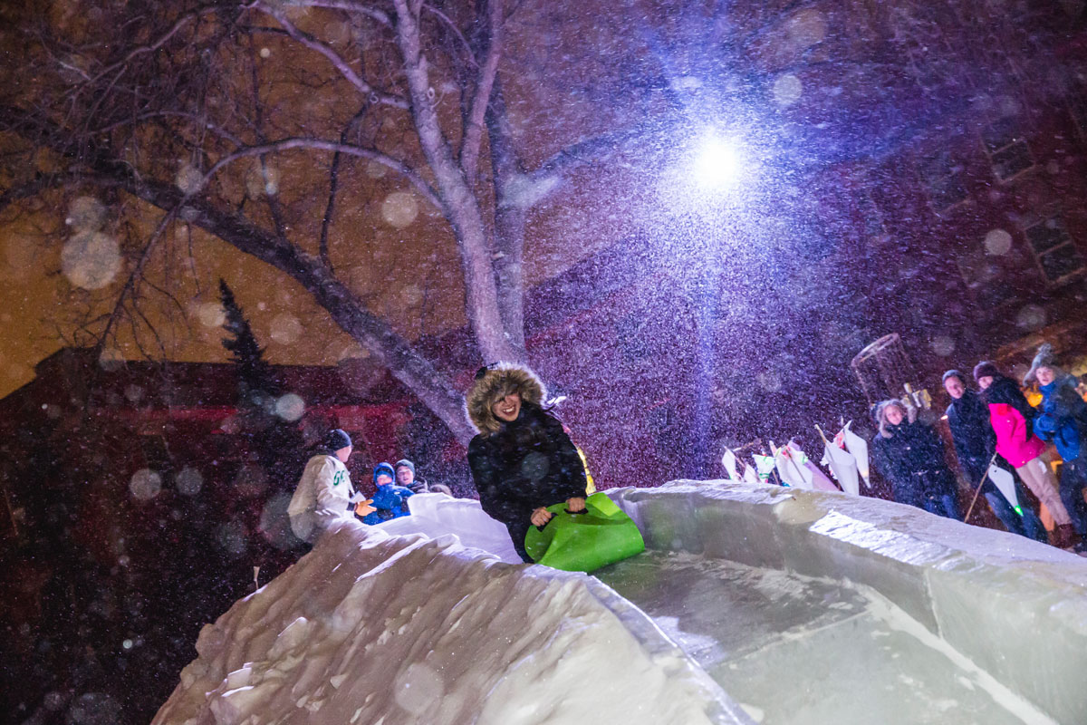 Crowds lined up in the falling snow to have a chance to zip down the ice slide