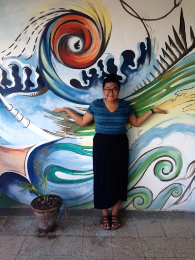 Jennifer Ha standing in front of a colourful wall mural in Cuba.