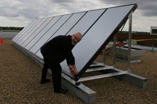 A photo of former Dean Roger Epp preparing to unveil a solar panel