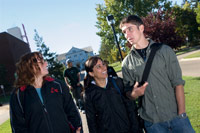 3 students talking on a sidewalk on campus