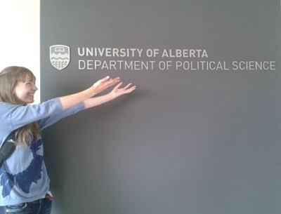 Wilissa Reist standing in front of and pointing to University of Alberta