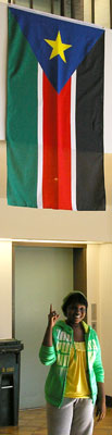A photo of a smiling student pointing to the flag of South Sudan