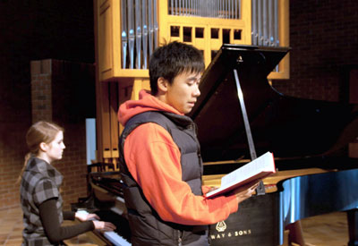 A photo of a student singing in the Chapel