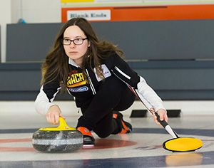 Sarah Brown throwing a stone in a curling rink