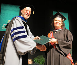 A photo of Dean Allen Berger shaking the hand of a student at graduation.
