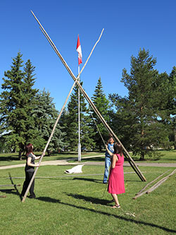 A photo of 3 people raising a tipi