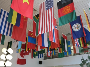 A scene of the many national flags that hang in the Faith & Life Lounge in the Forum