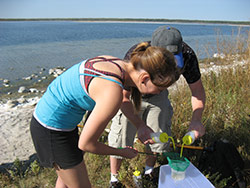 Two students doing field work on a lake shore.