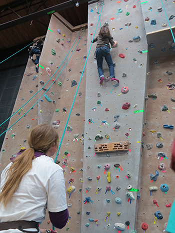 A photo of a person near the top of the climbing wall