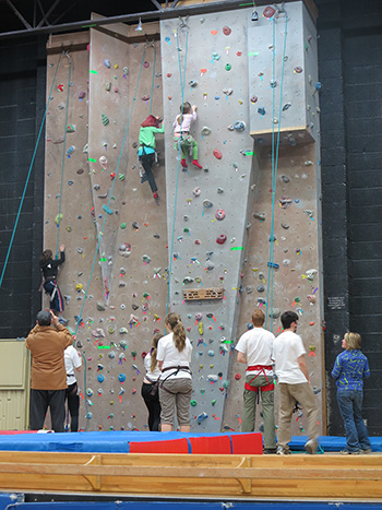 A photo of 2 people on the climbing wall, with a number of people on the floor below.