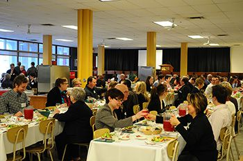 A photo of a full dining hall with tablecloths and people sitting at the tables.