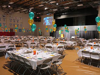 A photo of the gymnasium set up with tables for an awards event