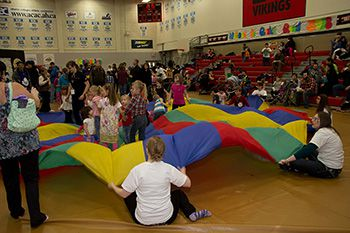 A photo of children and volunteers playing with a parachute