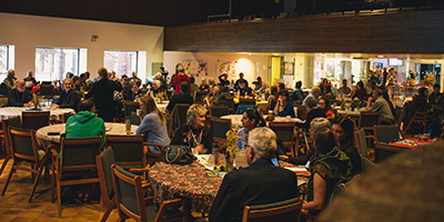 A photo of a large room of people sitting around conference tables
