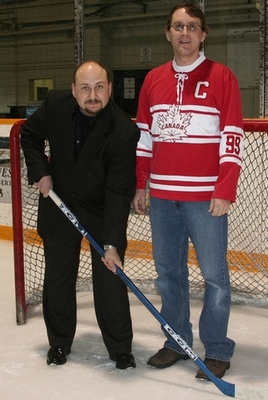 A photo of Bill Foster and Stacy Lorenz posing in front of a hockey net