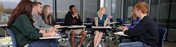 A photo of a professor talking to students in a small discussion group