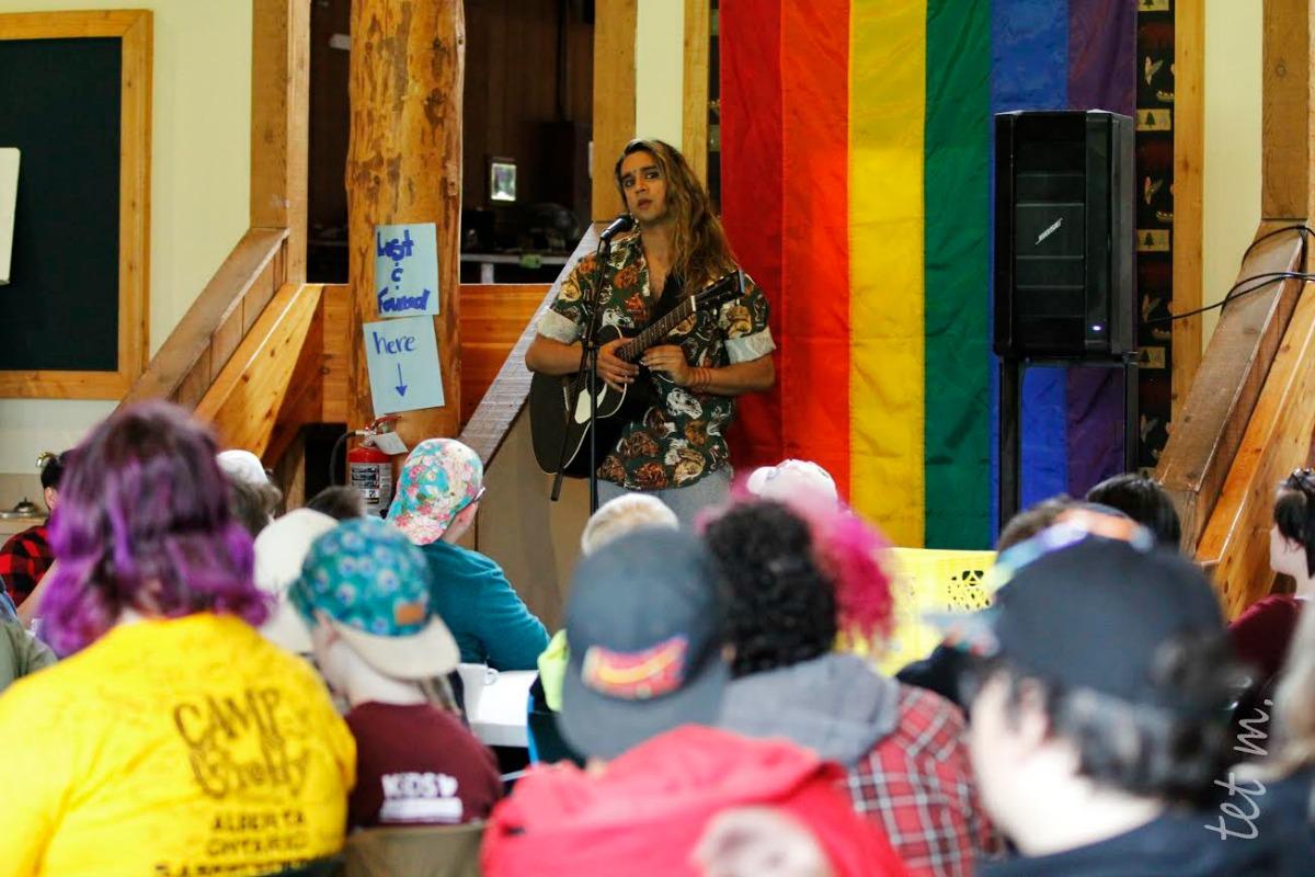Vivek Shraya with guitar iin front of a Pride flag at Camp fYrefly