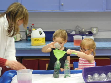 Two children and supervisor mix coloured liquids with funnel and bottles