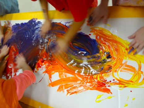 Close up of children actively finger painting