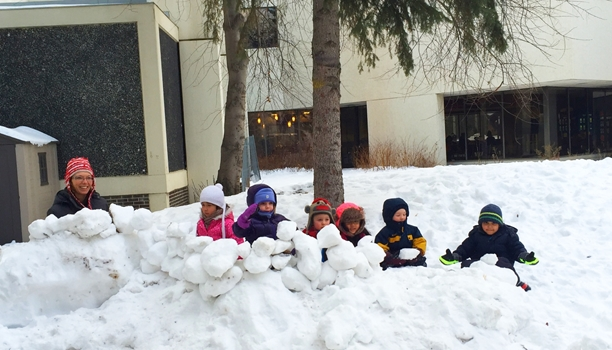 Children and supervisor outside hidden behind a snow fort