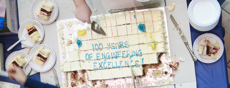 """Hands cutting a strawberry layer cake that is iced to read """"100 Years of Engineering Excellence"""""""