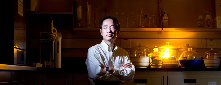 Coal Researcher in darkened lab with lab machinery behind him.