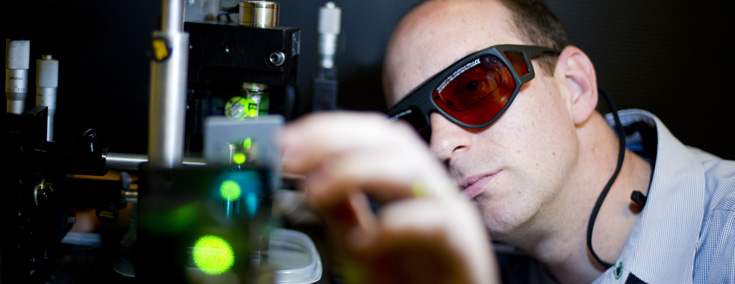 Engineer wearing safety glasses carefully adjusting a lab instrument that is emitting a green laser beam.