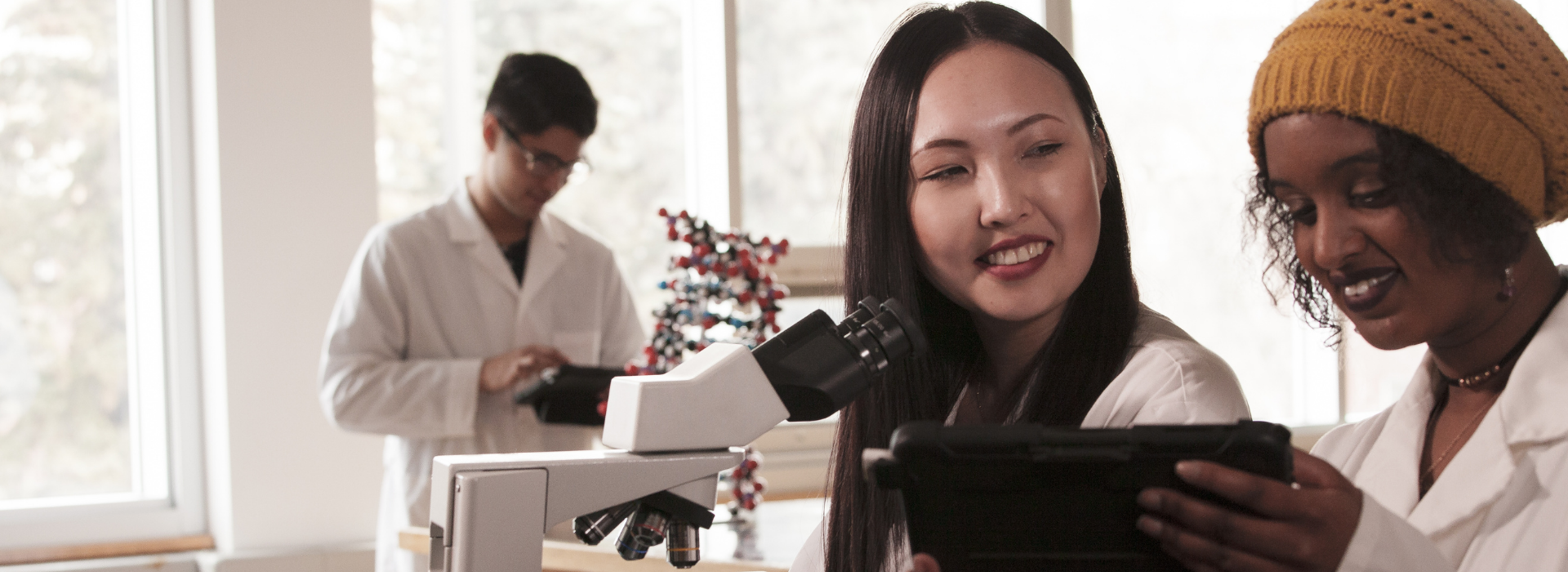 Two students in a CSJ laboratory in front of a microscope