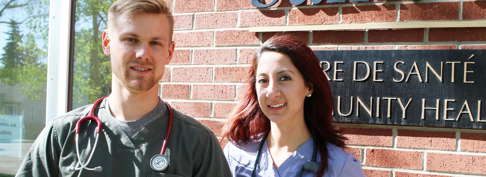 Two nursing students in front of Centre de Santé Saint-Thomas