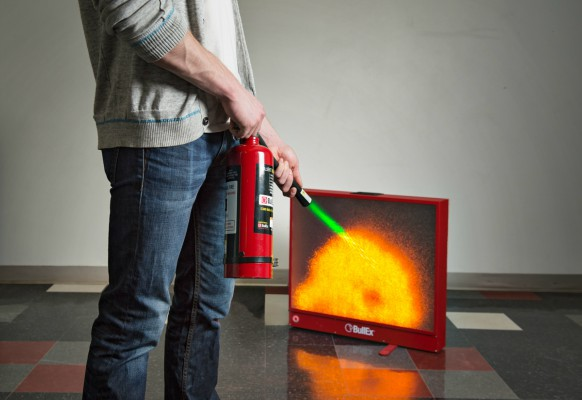 Person using fire extinguisher simulator