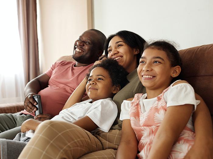 Smiling family sitting on sofa