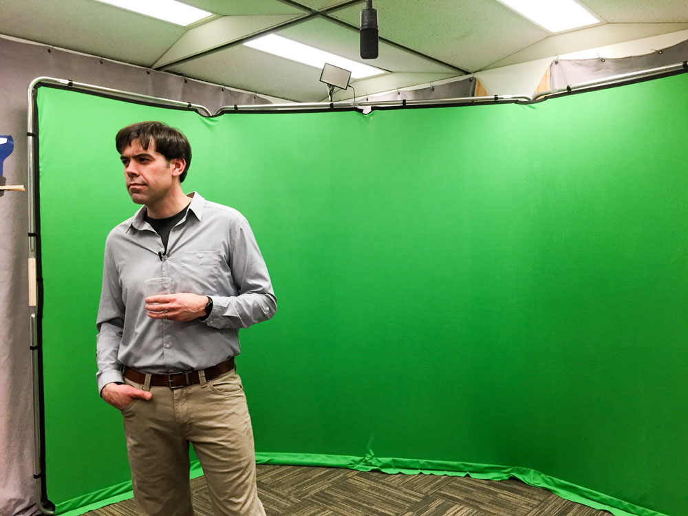 Dr. Zac Robinson filming for Mountains 101 in front of the green screen.