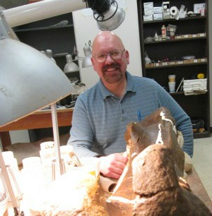 Howard Gibbons smiling at the camera as he prepares and cleans fossils in the Dino Lab