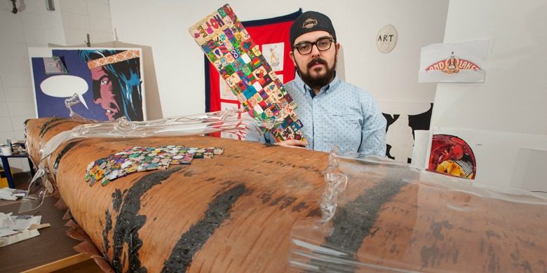 Jordan Bennett, UAlberta's indigenous artist-in-residence, shows off the birchbark canoe and tile-decorated paddle unveiled April 4 to commemorate the courage of former residential school students.