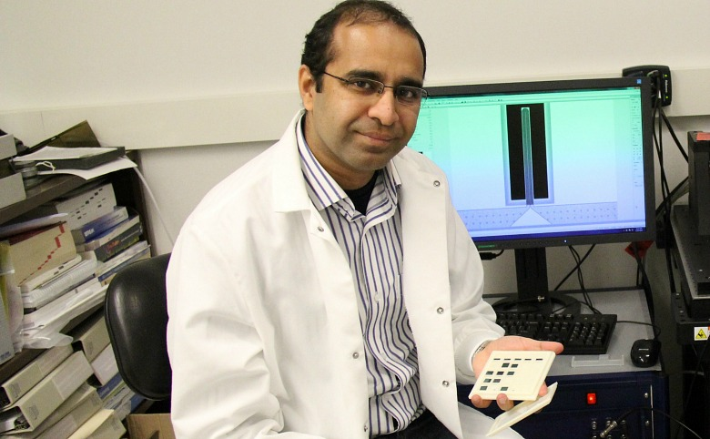 Post-doctoral fellow Faheem Khan with the newly developed bimetallic microchannel cantilever, a lab-on-a-chip sensor that can analyze liquids at a smaller volume than was previously possible