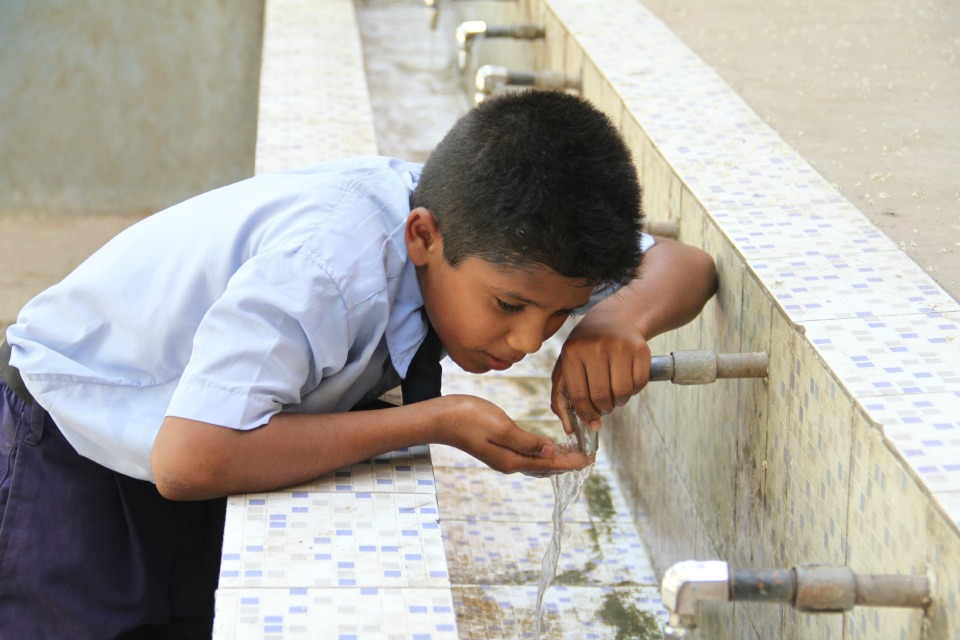 A young boy drinks from a water fountain in India (Photo courtesy IC-IMPACTS)