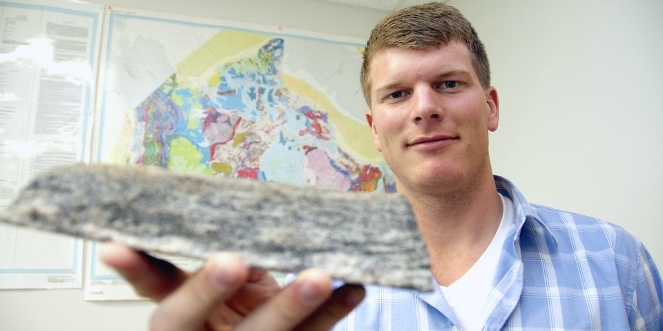 Jesse Reimink holds a sample of ancient rock from the Acasta Gneiss Complex in the Northwest Territories