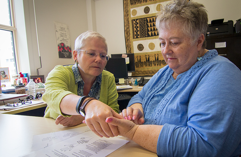 Researcher Cary Brown shows patient Nancy Cheyne how to apply shiatsu pressure massage to her hand.
