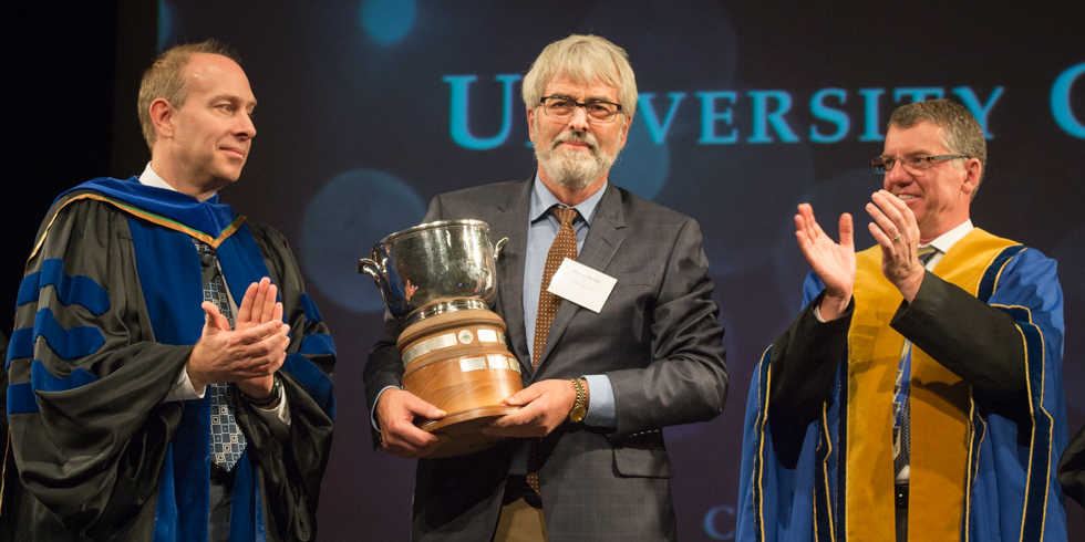 Sociology professor Harvey Krahn is congratulated by U of A president David Turpin and provost Steven Dew on receiving the University Cup.