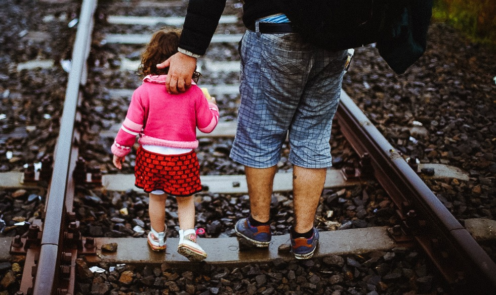 A refugee helps his daughter to run along a railway track after crossing the Serbian-Hungarian border.