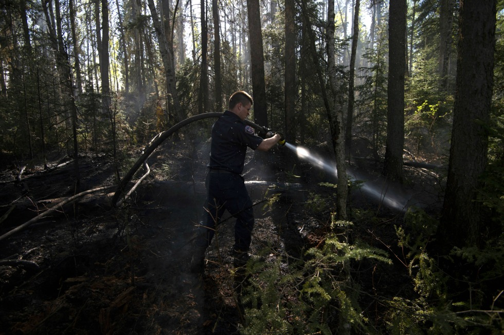 A Fort McMurray firefighter hoses down hotspots in the woods in the city limits on Sunday, May 15, 2016.