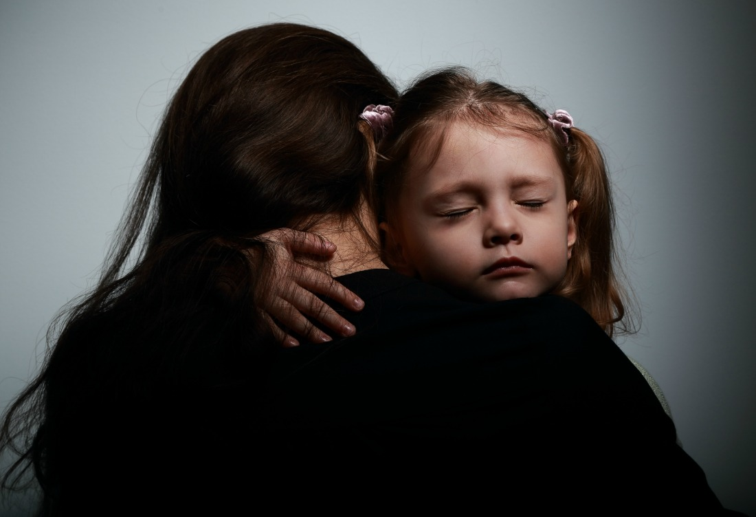 A mother comforts her young daughter.