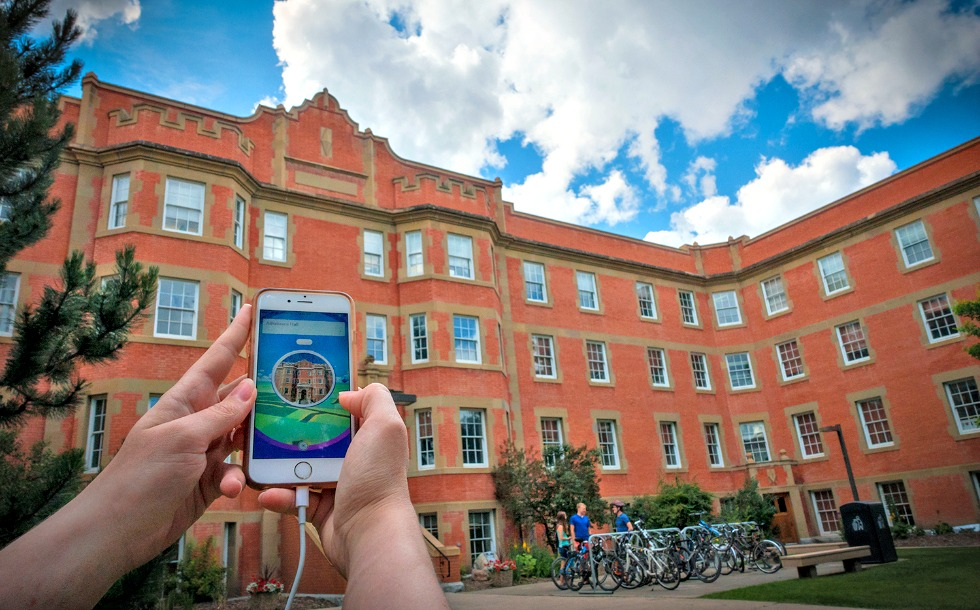 A Pokémon Go game player stops to replenish supplies at a PokéStop outside Athabasca Hall.