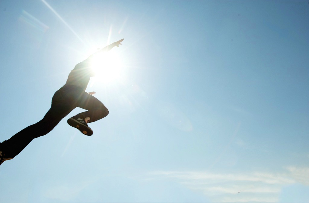 A UAlberta student leaps into the air on a sunny day.